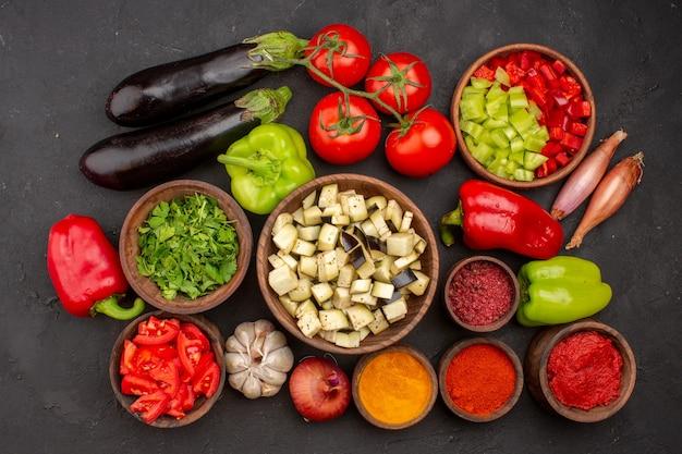 Widok z góry świeże warzywa z zieleniną i różnymi przyprawami na szarej ścianie sałatka ze zdrowej żywności warzywo