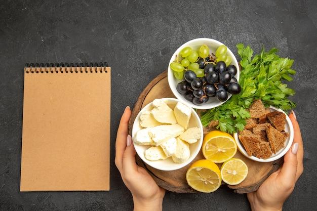 Widok z góry świeże winogrona z białym serem plasterki cytryny i zielenie na ciemnej powierzchni jedzenie mąka owoce mleczne