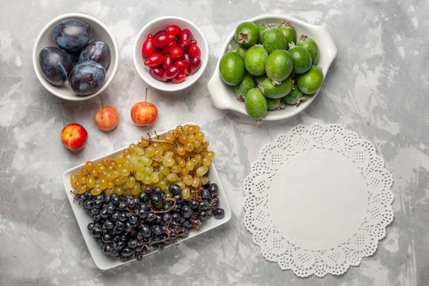 Widok z góry świeże winogrona z feijoa i derenie na białej powierzchni owocowy łagodny sok witaminowy