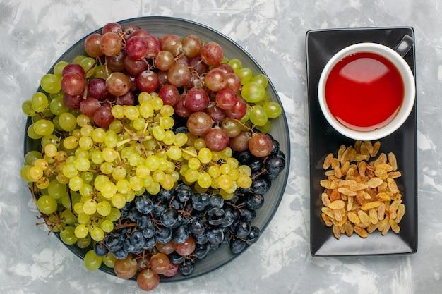 Widok z góry świeże winogrona z filiżanką herbaty i rodzynkami na białej powierzchni owoce świeża herbata winogronowa