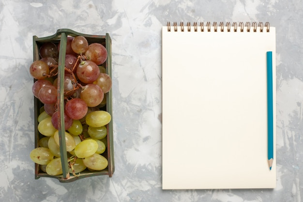Widok z góry świeże winogrona z notatnikiem na białym tle owoce łagodne soczyste świeże