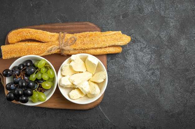 Widok z góry świeże winogrona z serem i chlebem na ciemnym biurku owoce łagodne dojrzałe drzewo witaminowe mleko spożywcze