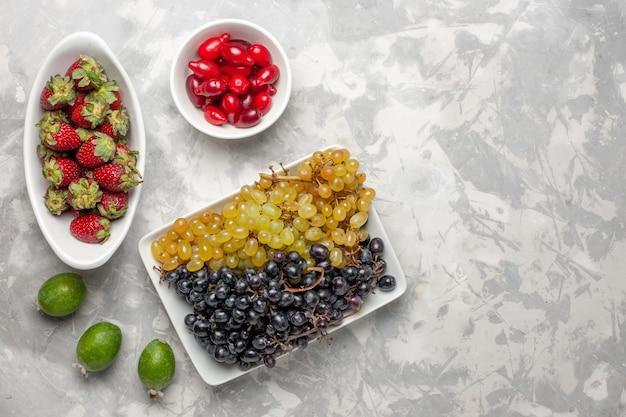 Widok z góry świeże winogrona z truskawkami i derenie na białej powierzchni owoc łagodny sok witaminowy