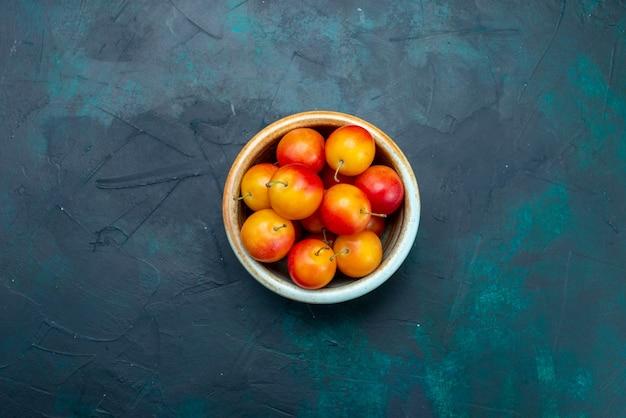 Widok z góry świeże wiśnie śliwki kwaśne i łagodne owoce w małym garnku na ciemnoniebieskim tle owocowe łagodne świeże witamina