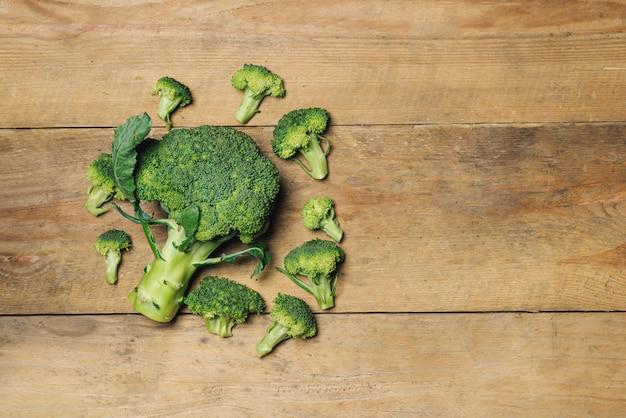 Widok z góry świeże zielone brokuły na rustykalne drewniane tła - zdrowe lub wegetariańskie jedzenie.