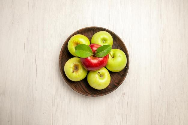 Widok z góry świeże zielone jabłka dojrzałe i aksamitne owoce na białym biurku kolor owoców świeża roślina czerwone drzewo