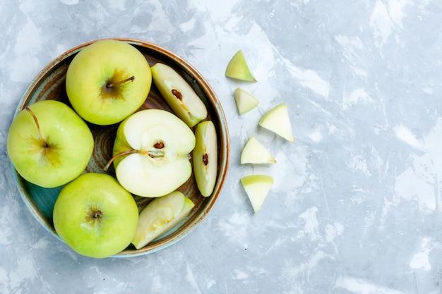 Widok z góry świeże zielone jabłka w plasterkach i całe owoce na jasnobiałej powierzchni