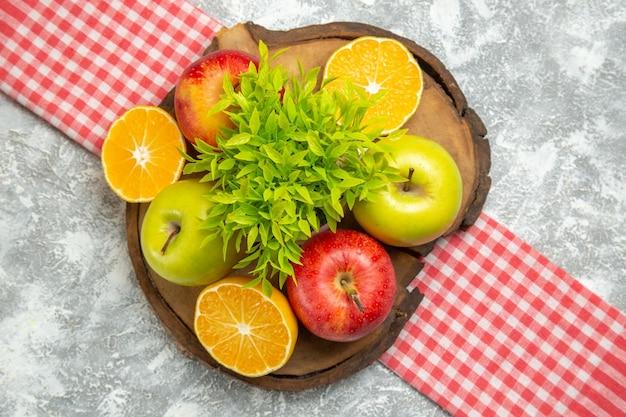 Widok z góry świeże zielone jabłka z pokrojonymi pomarańczami na białej powierzchni owoce jabłka dojrzałe aksamitne świeże