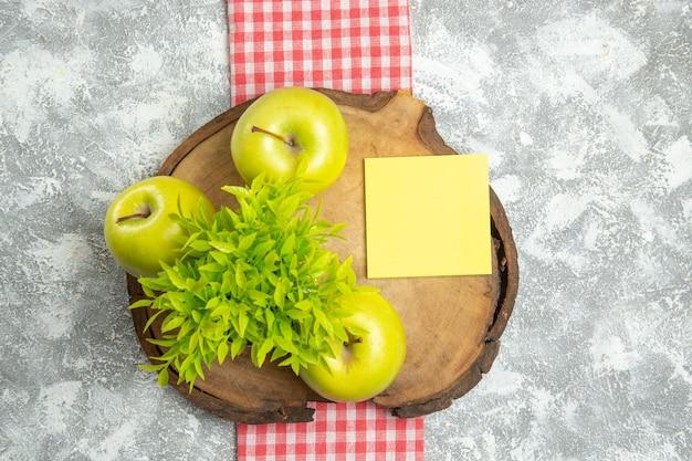 Widok z góry świeże zielone jabłka z zieloną rośliną na białej powierzchni owoce jabłka dojrzałe łagodne świeże