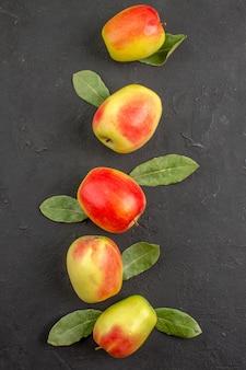 Widok z góry świeże zielone jabłka z zielonymi liśćmi na ciemnym stole dojrzałe dojrzałe drzewo