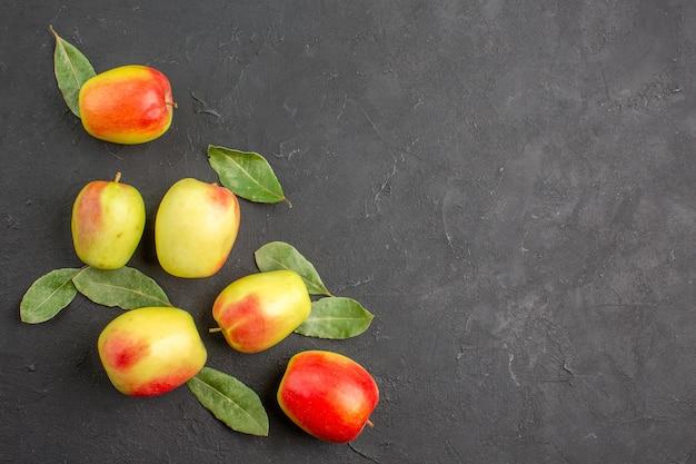 Widok z góry świeże zielone jabłka z zielonymi liśćmi na ciemnym stole drzewo łagodnie dojrzałe świeże
