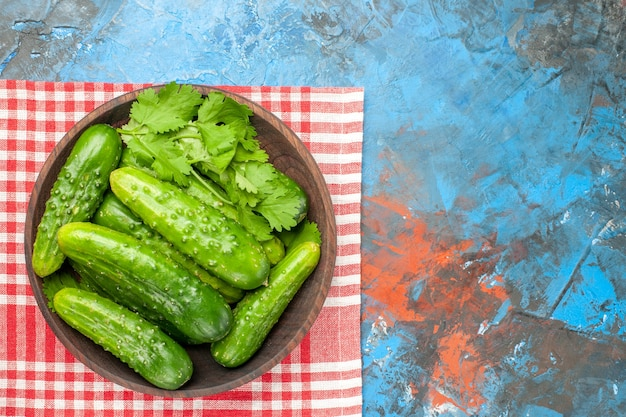 Widok z góry świeże zielone ogórki wewnątrz talerza na niebieskim tle