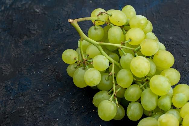 Widok z góry świeże zielone winogrona kwaśne soczyste i łagodne na ciemnym tle dojrzałych owoców roślin