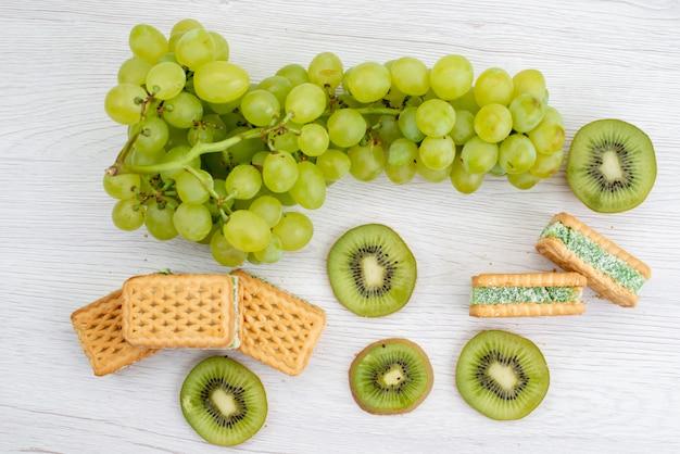 Widok z góry świeże zielone winogrona kwaśne soczyste i łagodne z ciasteczkami i owocami kiwi dojrzałe zielone rośliny