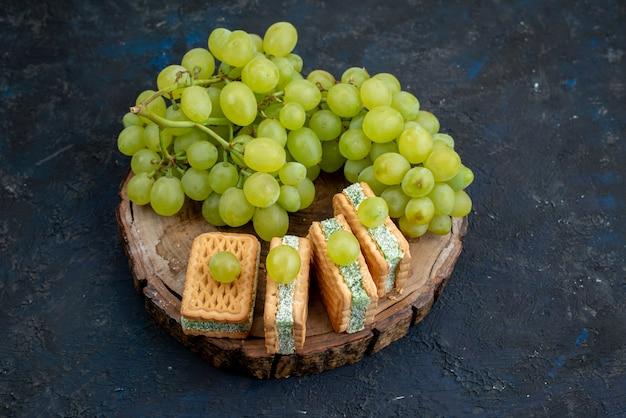 Widok z góry świeże zielone winogrona kwaśne soczyste i łagodne z ciasteczkami na ciemnym tle dojrzałe zielone owoce roślin