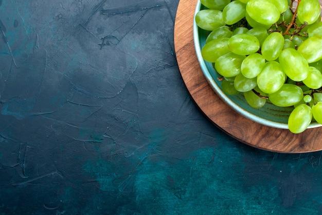 Widok z góry świeże zielone winogrona łagodne soczyste owoce wewnątrz talerza na granatowym biurku.