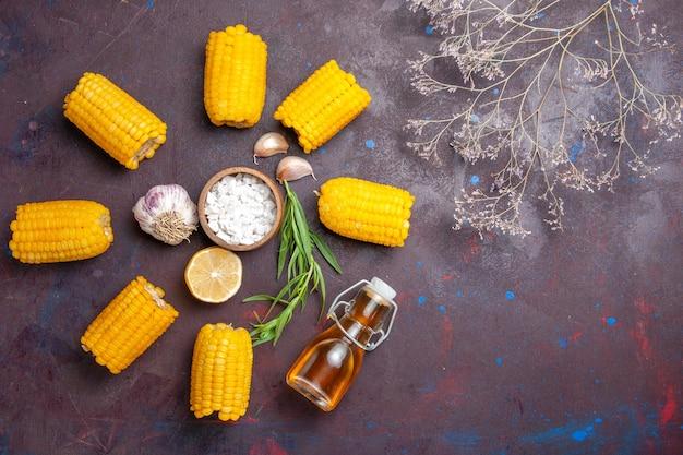 Widok z góry świeże żółte odciski surowe z olejem na ciemnej powierzchni kukurydziana przekąska surowa świeża