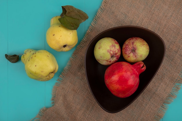 Widok z góry świeżego granatu z jabłkami na miskę na worek szmatką z pigwy na białym tle na niebieskim tle
