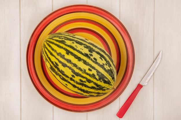 Widok z góry świeżego melona kantalupa na talerzu z nożem na białej drewnianej ścianie