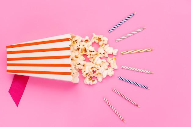 Widok z góry świeżego popcornu wewnątrz opakowania papieru na białym tle wraz z kolorowymi świecami na różowej, filmowej przekąsce nasion kukurydzy