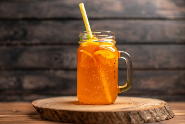 Widok z góry świeżego soku pomarańczowego w szklance z rurką na drewnianej tacy na brązowym tle