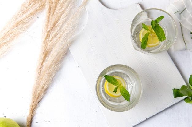 Widok z góry świeżej, chłodnej lemoniady z pokrojonymi cytrynami wewnątrz szklanek na białej powierzchni