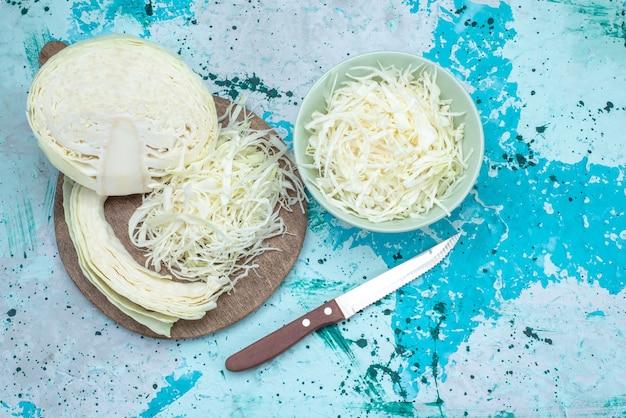 Widok z góry świeżej kapusty pokrojonej w plasterki z połową całych warzyw na jasnoniebieskim biurku, przekąska z warzywami, zdrowa sałatka