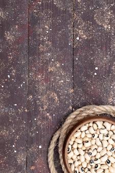 Widok z góry świeżej surowej fasoli wewnątrz brązowej miski z sznurem na brązowym drewnianym fasoli surowej fasoli