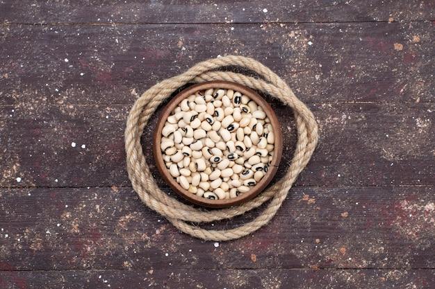 Widok z góry świeżej surowej fasoli wewnątrz brązowej miski z sznurem na brązowym, surowej fasoli fasoli