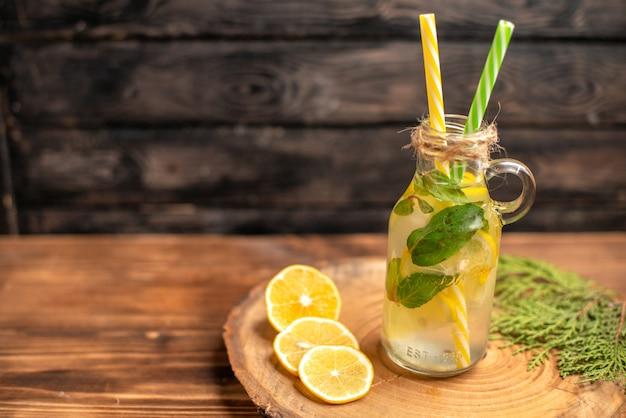 Widok z góry świeżej wody detoksykującej w szklance podawanej z rurkami i limonkami cytrynowymi po lewej stronie na brązowej tacy