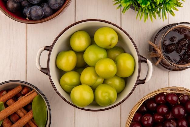 Widok z góry świeżej zielonej śliwki wiśniowej na misce z wiśniami na wiadrze z dżemem truskawkowym na szklanym słoju na białym drewnianym tle