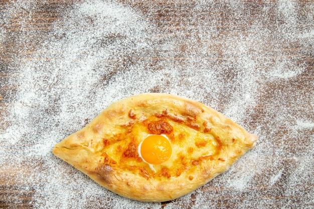 Widok Z Góry świeżo Upieczony Chleb Z Gotowanym Jajkiem I Mąką Na Brązowej Powierzchni Ciasto Upiec Bułkę Mąkę Jajko Darmowe Zdjęcia