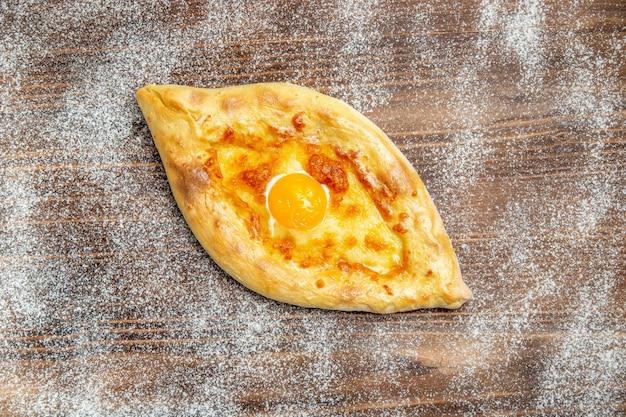 Widok z góry świeżo upieczony chleb z gotowanym jajkiem na brązowym biurku ciasto jedzenie upiec bułkę posiłek jajko