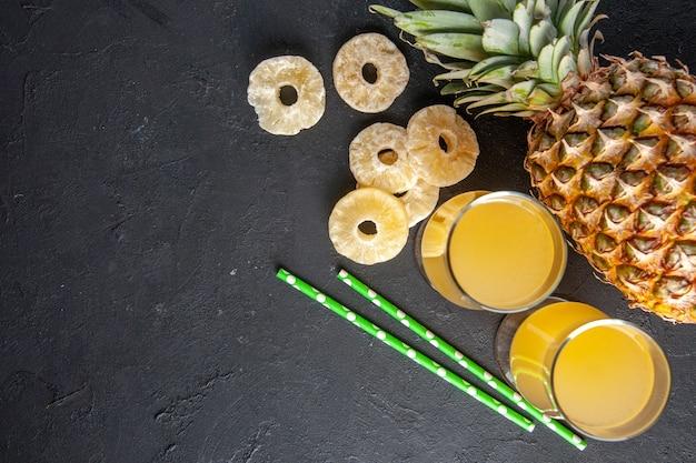 Widok z góry świeży ananas leżący suche plasterki ananasa sok ananasowy w szklankach na ciemnym tle miejsce kopiowania