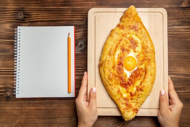 Widok z góry świeży chleb z gotowanym jajkiem na drewnianym biurku chleb ciasto mąka bułka jedzenie śniadanie jajka