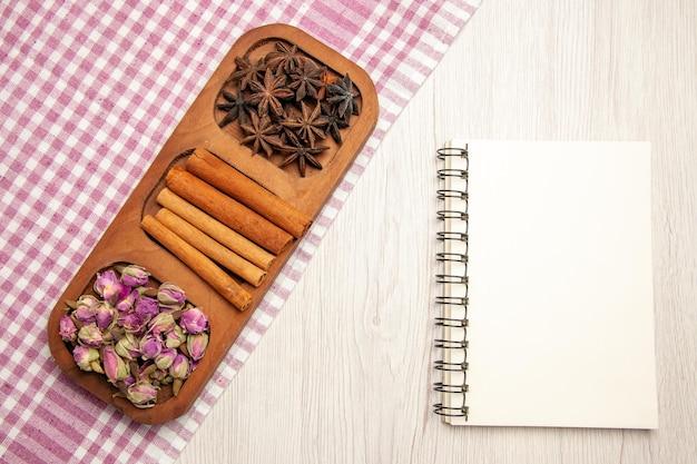 Widok z góry świeży cynamon z kwiatami i notatnikiem na białym biurku w kolorze roślin kwiatowych