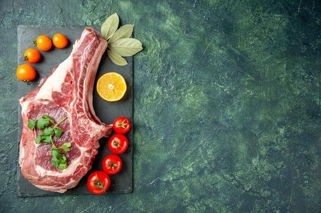 Widok z góry świeży kawałek mięsa z pomidorami na ciemnoniebieskim tle jedzenie mięso kuchnia zwierzę krowa rzeźnik kurczak kolor wolna przestrzeń