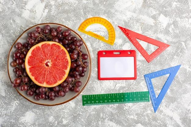 Widok z góry świeży pierścień grejpfrutowy z czerwonymi winogronami i postaciami na białej powierzchni