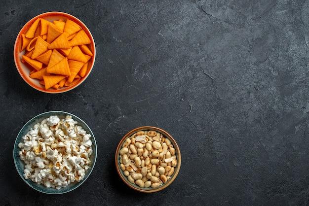 Widok z góry świeży popcorn z orzechami i frytkami na ciemnym tle chips przekąska chrupki krakers