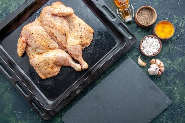Widok z góry świeży przyprawiony kurczak z przyprawami na ciemnoniebieskim tle jedzenie przyprawa pieprz danie obiad mięso kolor sól do pieczenia