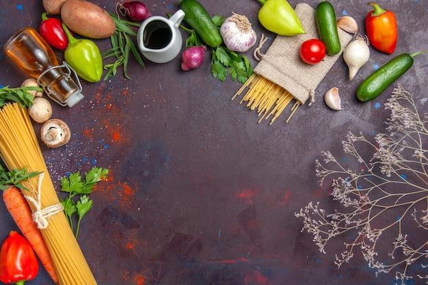 Widok z góry świeży surowy makaron z warzywami na ciemnej powierzchni sałatka jedzenie zdrowy posiłek warzywny