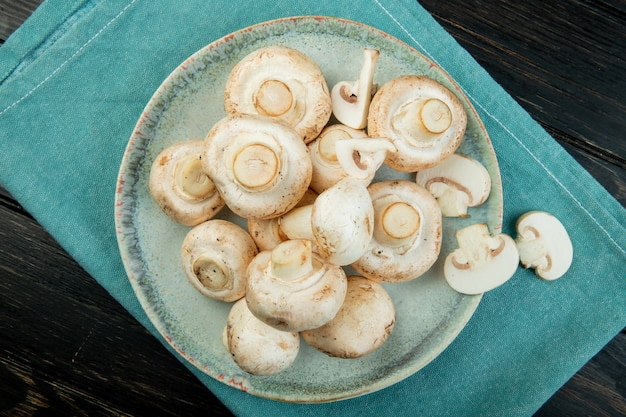 Widok z góry świeżych białych grzybów na niebieskim talerzu na ciemnej powierzchni drewnianej