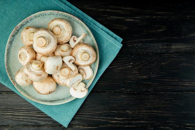 Widok z góry świeżych białych grzybów na niebieskim talerzu na ciemnym drewnie z miejsca na kopię