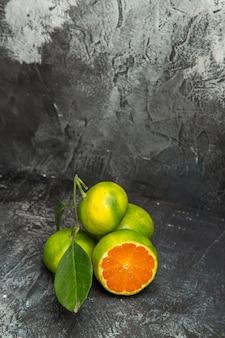 Widok z góry świeżych całych zielonych mandarynek z liśćmi i jeden przecięty na pół mandarynki na szarym tle materiału