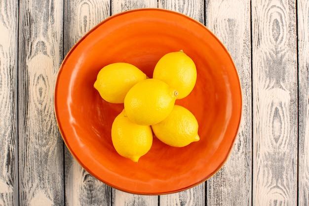 Widok z góry świeżych cytryn kwaśnych dojrzałych łagodnych soczystych cytrusów wewnątrz pomarańczowego talerza witaminowy żółty na szarym rustykalnym biurku