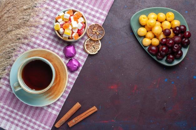 Widok z góry świeżych czereśni wewnątrz talerza z cukierkami i herbatą cynamonową na ciemnej powierzchni