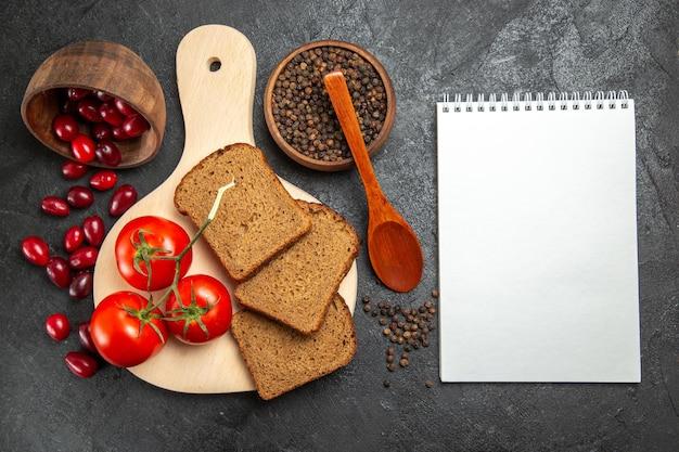 Widok z góry świeżych czerwonych dereni z bochenkami chleba i pomidorami na szarej powierzchni