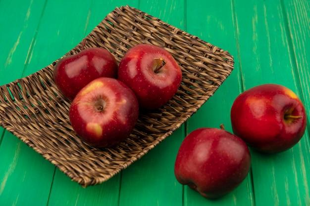 Widok z góry świeżych czerwonych jabłek na tacy wikliny na zielonej drewnianej ścianie