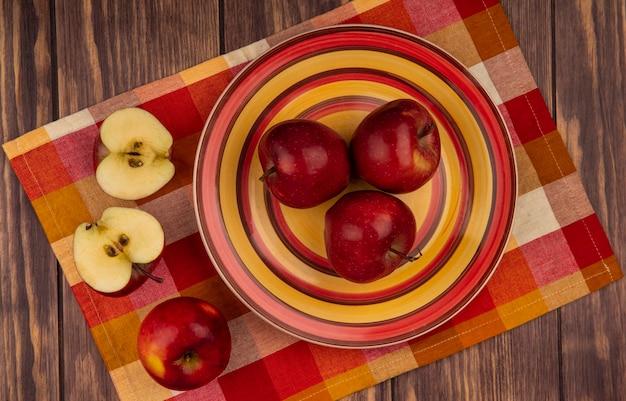 Widok z góry świeżych czerwonych jabłek na talerzu na szmatce w kratkę z przepołowionymi jabłkami odizolowanymi na drewnianej ścianie
