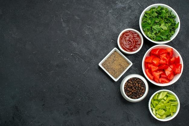 Widok z góry świeżych czerwonych pomidorów pokrojonych w plasterki warzyw z zielenią na czarnym stole